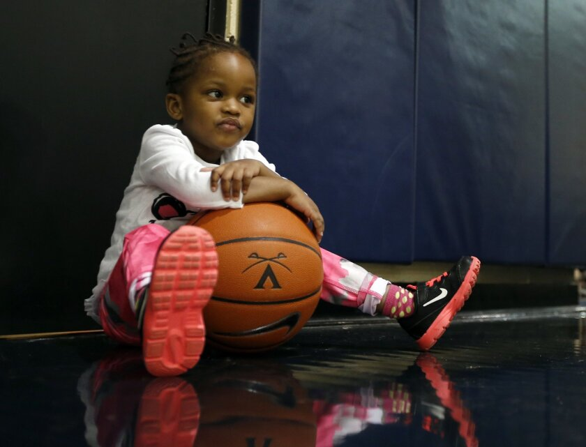 In this Jan. 27, 2015, photo, Ngoty, of Senegal, the adopted daughter of Viginia women's basketball coach Joanne Boyle, rests on a basketball as she plays with members of the women's basketball team in Charlottesville, Va. Each trip to Senegal to try and adopt Ngoty entailed an eight-hour flight to