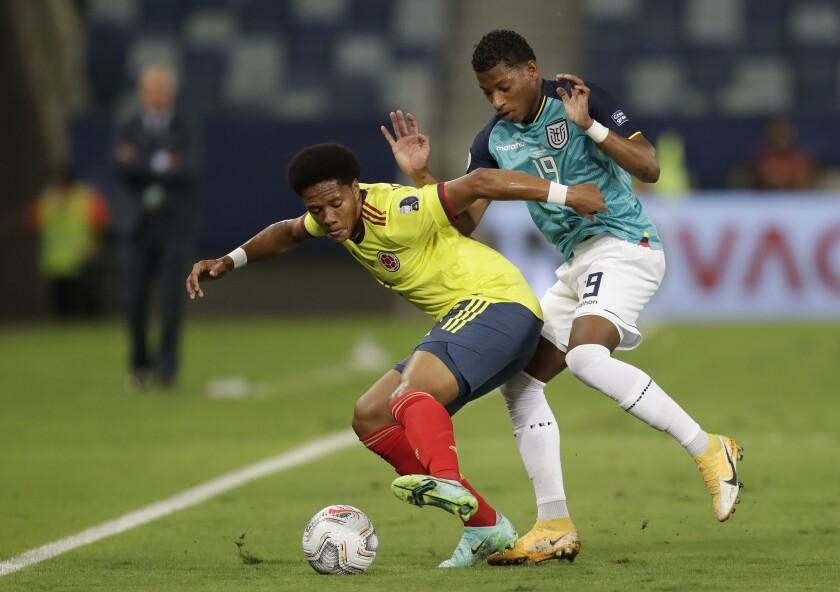 El lateral colombiano Yairo Moreno (izquierda) pugna un balón con el ecuatoriano Gonzalo Plata