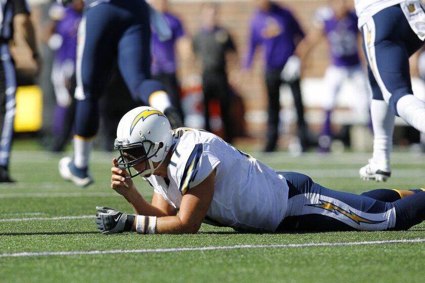 Chargers Philip Rivers lays on the ground after throwing an interception for a touchdown by Vikings Chad Greenway.