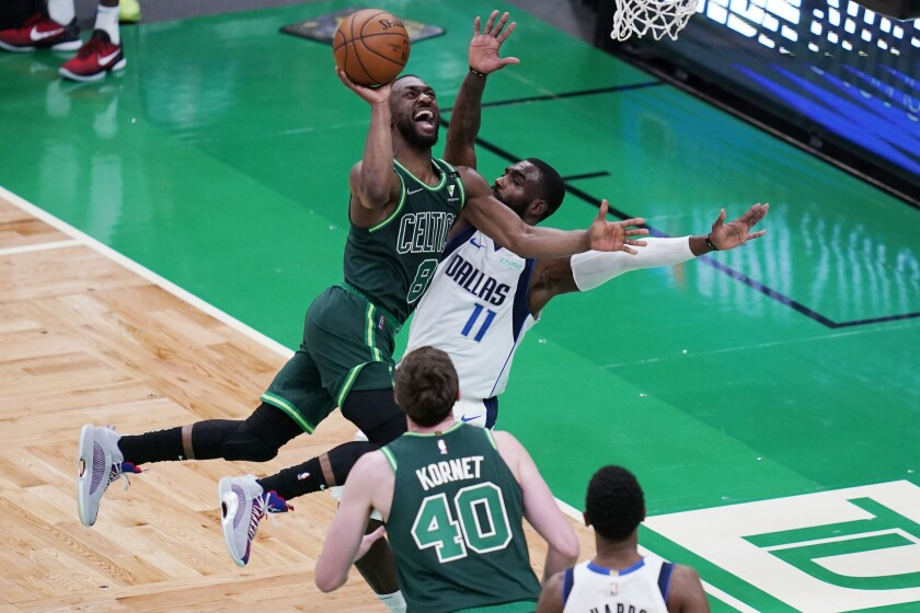 FILE - Boston Celtics guard Kemba Walker (8) collides with Dallas Mavericks forward Tim Hardaway Jr. (11) on a drive to the basket during an NBA basketball game in Boston, in this Wednesday, March 31, 2021, file photo. Kemba Walker and the Oklahoma City Thunder have agreed to a buyout of the final two years of his contract, and once that is completed the four-time All-Star guard will sign with the New York Knicks, a person with knowledge of the situation said Wednesday, Aug. 4, 2021. He never played for the Thunder, who acquired him in a trade with Boston in June in the deal that sent Al Horford back to the Celtics. (AP Photo/Charles Krupa, FIle)