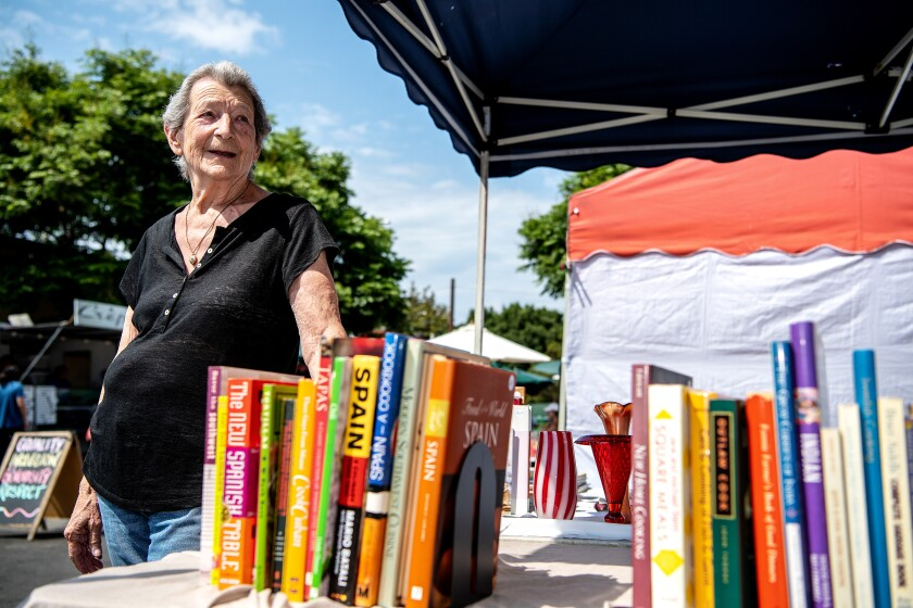 A woman stands next to a table filled with cookbooks.