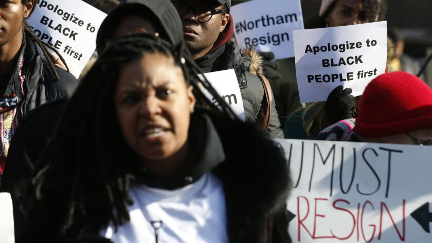 Demonstrators hold signs and chant outside the Governors Mansion at the Capitol in Richmond, Va., Sa
