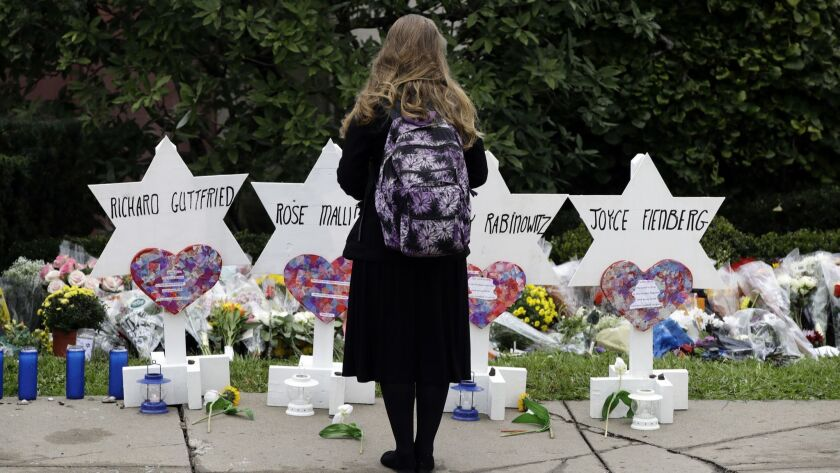 A person stands in front of Stars of David that are displayed in front of the Tree of Life Synagogue