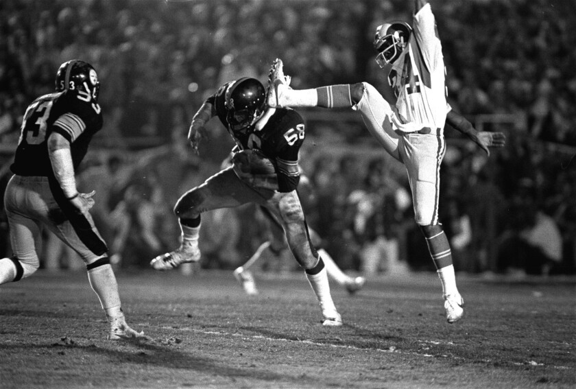 Steelers linebacker Jack Lambert (58) comes down under the foot of Los Angeles Rams receiver Ron Smith (84) after intercepting a pass in the fourth quarter of Super Bowl XIV in 1980.