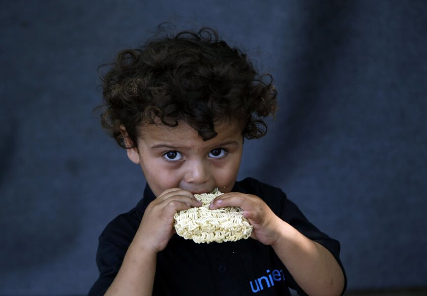 A migrant child eats at a makeshift camp for migrants in Horgos, Serbia, meters away from Serbia's border with Hungary, Thursday, Aug. 25, 2016. Officials say Hungary's police could join the Serbian troops patrolling the Balkan country's border with Macedonia or Bulgaria to help curb the influx of