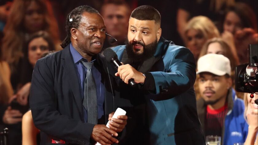 DJ Khaled, right, gets a stagehand to help him as host of Sunday's iHeartRadio Music Awards.