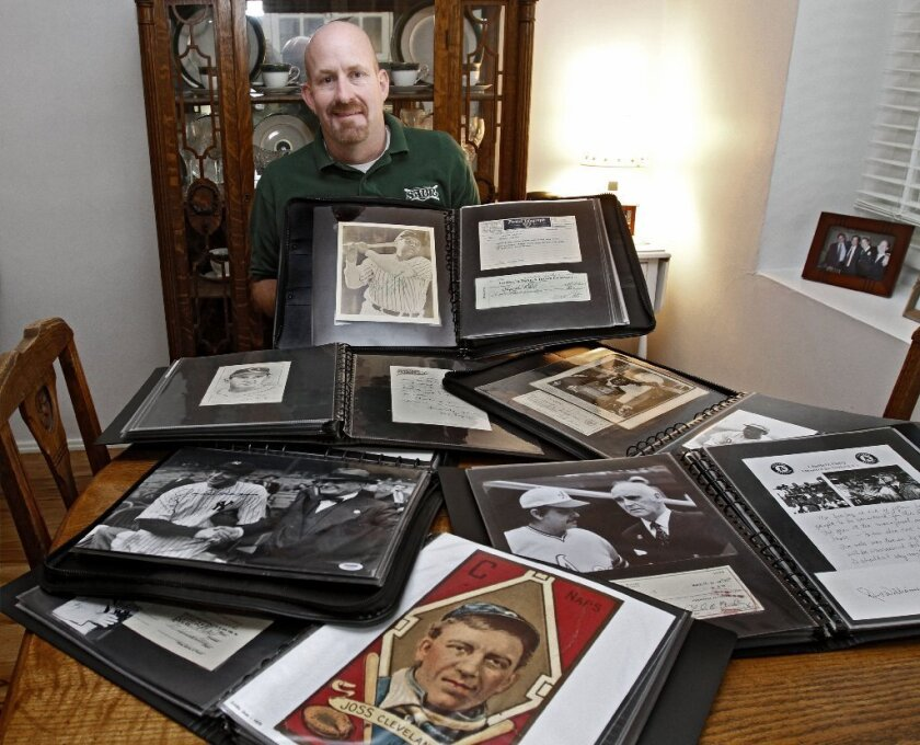 Crescenta Valley High teacher and former Falcons boys' basketball coach Jim Smiley shows off part of his extensive baseball collection.