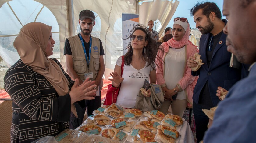 Eman Awadallah, far left, a mother of three, talks to members of the United Nations Development Program and the U.N. Foundation's Global Entrepreneurs Council about the bread and pastry business she established with seed money through a project sponsored by UNDP.