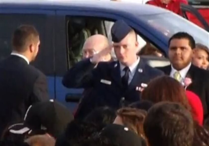 In this still image taken from an April 20, 2013 video provided by Tammy Garth, Airman Cassey Widener salutes as his sister, Courtrney Widener, arrives for prom at Liberal High School in Liberal, Kan. Courtney wanted her brother, recently returned from Afghanistan, to escort her to front door of th