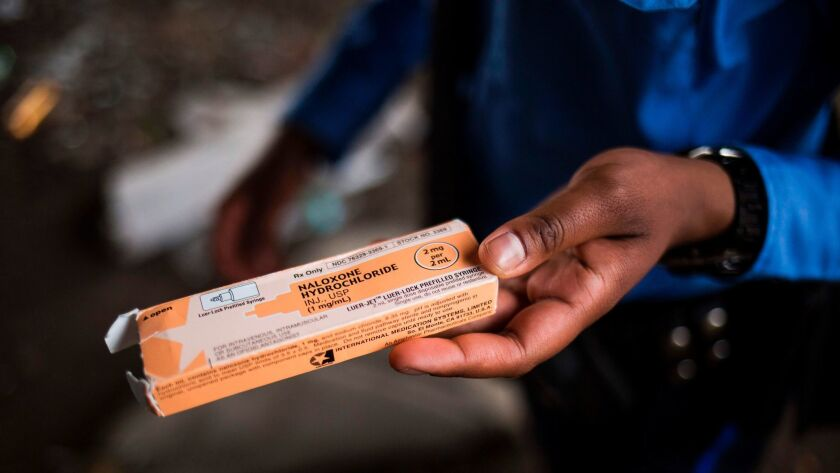 A Philadelphia police officer holds a package of the overdose reversal agent naloxone hydrochloride,