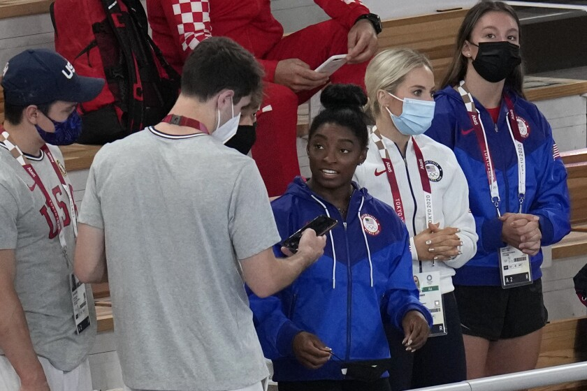 Simone Biles, of the United States, center in blue, looks on with teammates during the women's floor exercise in artistic gymnastics at the 2020 Summer Olympics, Monday, Aug. 2, 2021, in Tokyo, Japan. (AP Photo/Gregory Bull)