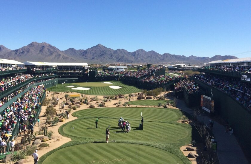 In this Saturday, Feb. 5, 2016, photo, golfers and caddies gather on the 16th green during the third round of the  Phoenix Open golf tournament at TPC Scottsdale in Scottsdale, Ariz. A picturesque par-3 for 51 weeks, No. 16 at TPC Scottsdale transforms into a golf version of a party cruise the week