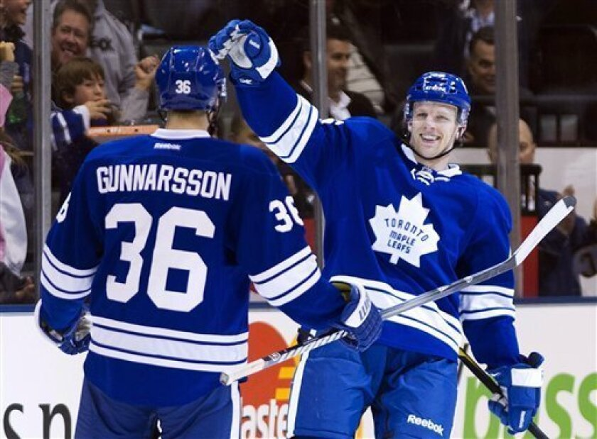 Toronto Maple Leafs forward Joey Crabb, right, celebrates his short-handed goal with defenseman Carl Gunnarsson left, against the Buffalo Sabres during the first period of an NHL hockey game in Toronto on Saturday, March 31, 2012. (AP Photo/The Canadian Press, Nathan Denette)