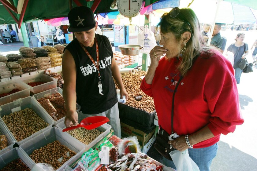 Dixie Miller tastes a Japanese peanut from vendor Miguel Arroyo's stall on Wednesday at the Escondido Swap Meet. The swap meet's 560 vendors offer everything from live animals and clothing to jewelry and food.