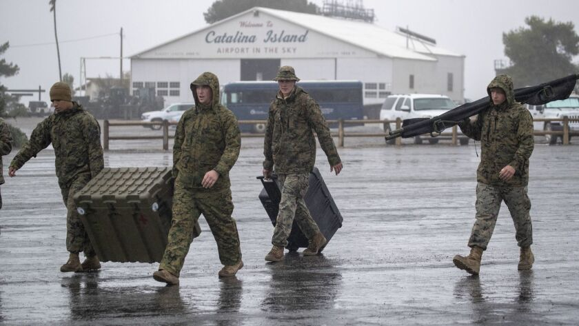Marines from the 3rd Marine Aircraft Wing carry supplies to tents at Airport in the Sky on Santa Catalina Island.