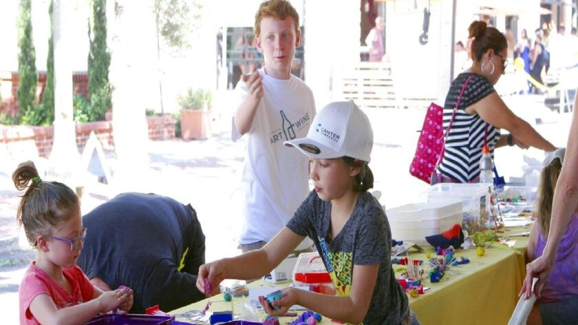 Kids make their own art in the Geppetto's Toys' family art tent.