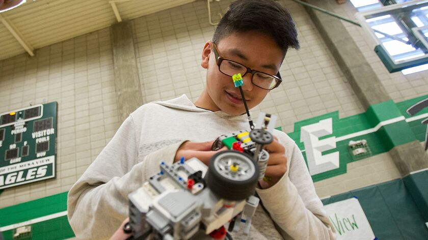 Ben Nguyen, 13, from Vista View Middle School in Fountain Valley makes adjustments to a Sumo Bot rob