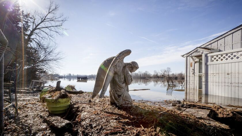 An angel statuary graces a yard near Hansen Lake Friday, March 22, 2019, in Bellevue, Neb. Residents