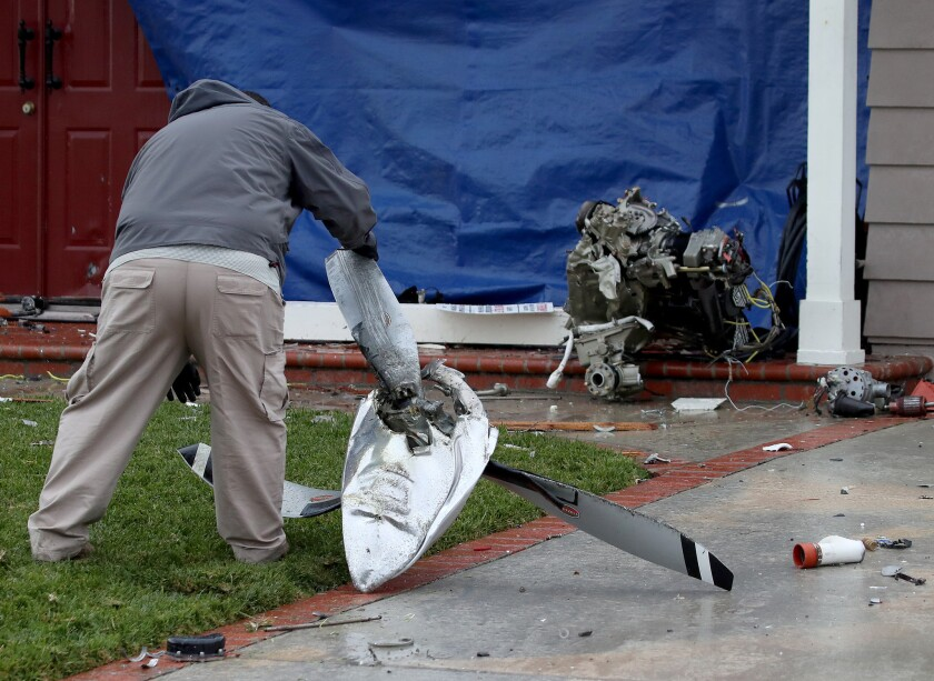 Air safety investigator Ricardo Asensio inspects the propeller and other pieces from a Cessna airplane outside a Yorba Linda home.