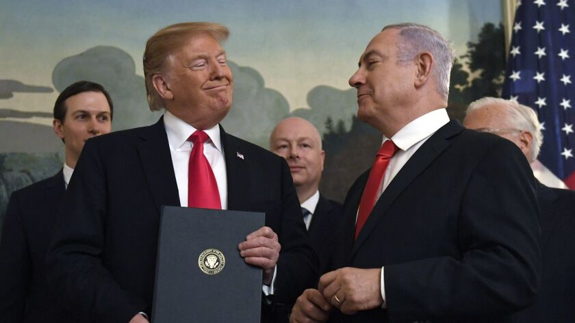 President Donald Trump smiles at Israeli Prime Minister Benjamin Netanyahu, right, at the White House in Washington on March 25.