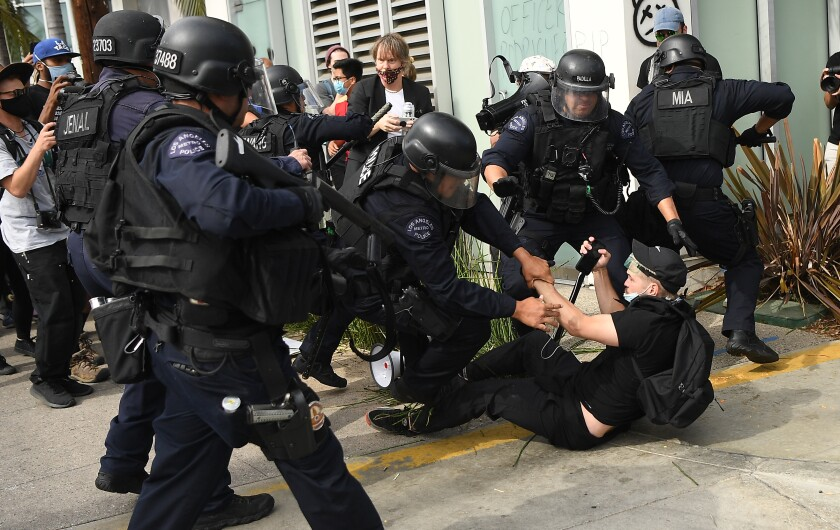 LAPD officers arrest a protester in the Fairfax District of Los Angeles.