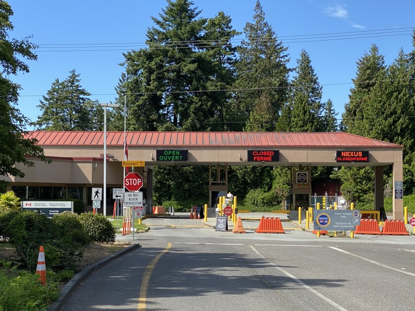 A single lane is open and empty at a border crossing.