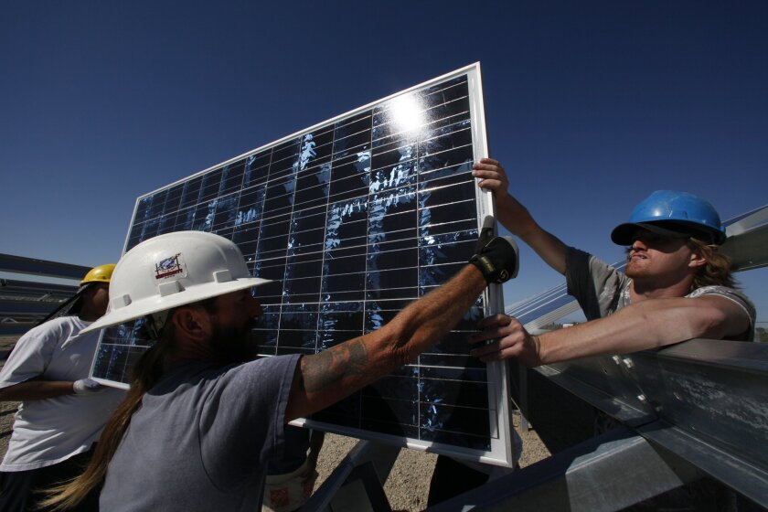 Melvin Hale (left) hands a solar panel to Chase Gordon for installation at a solar farm in Niland, in the Imperial Valley. Peggy Peattie • U-T