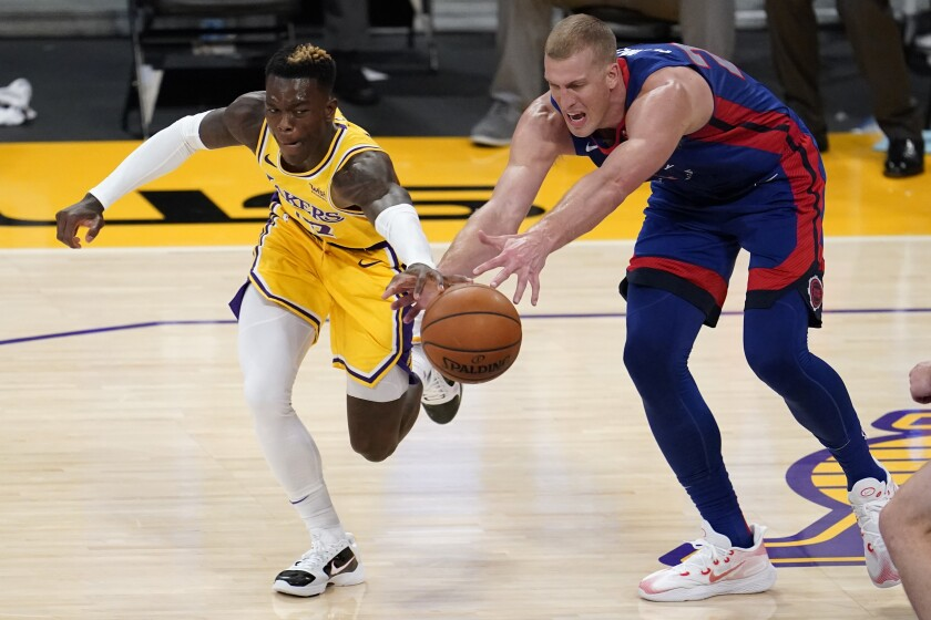 Lakers guard Dennis Schroder chases after a loose ball against Pistons center Mason Plumlee.