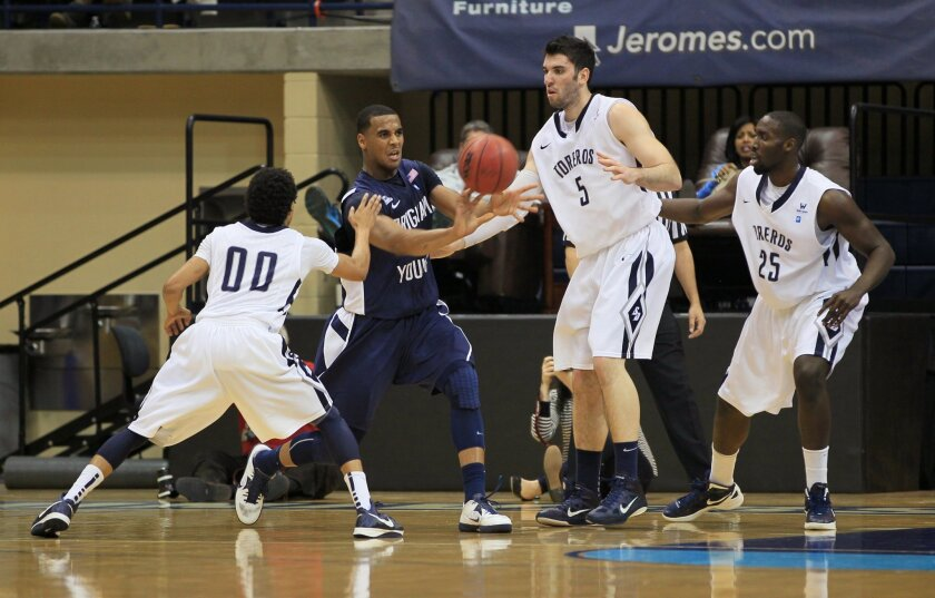 BYU's Brandon Davies is boxed in by USD's, LtoR: Christopher Anderson, Chris Manresa, and Simi Fajemisin.