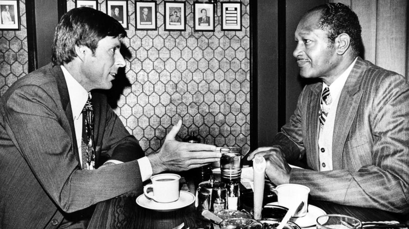 Sen. John Tunney, left, and L.A. Mayor Tom Bradley discuss the energy crisis over breakfast at a downtown restaurant in January 1974.