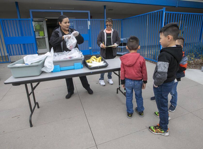 Students received their grab-and-go school breakfasts at La Mirada Elementary School, part of the San Ysidro School District, on Monday, March 16, 2020, the first day of school closures under the COVID-19 virus school shutdown.