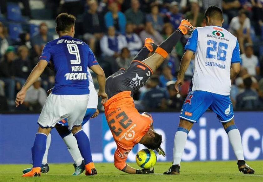 El jugador de Cruz Azul Felipe Mora (i) disputa un balón frente a Moises Muñoz (c) de Puebla durante el juego correspondiente a la jornada 8 del torneo mexicano celebrado en el estadio Azul de Ciudad de México (México). EFE