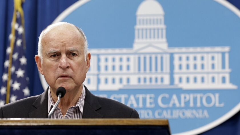 Gov. Jerry Brown listens to questions about his revised 2018-19 state budget at a Capitol news conference May 11.