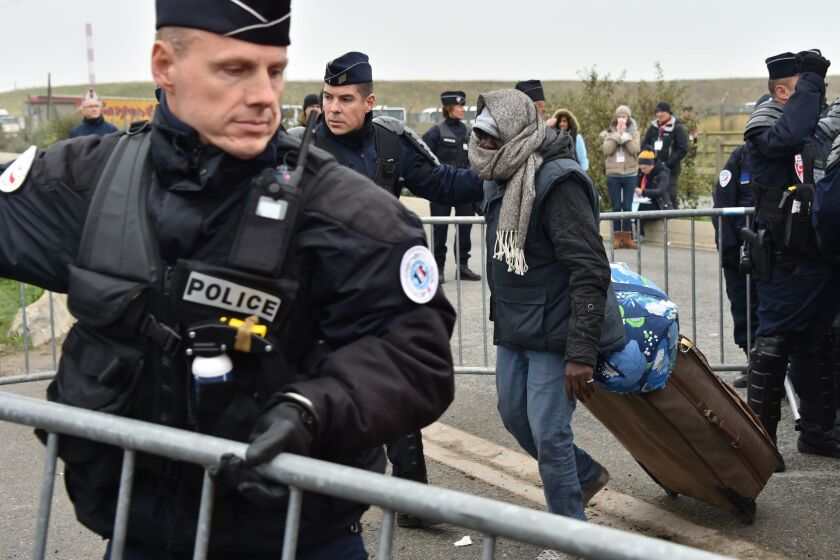 """French riot police officers let a migrant go with his suitcase on Oct. 24, 2016, as part of a major three-day operation planned to clear the """"Jungle"""" migrant camp in Calais. ="""
