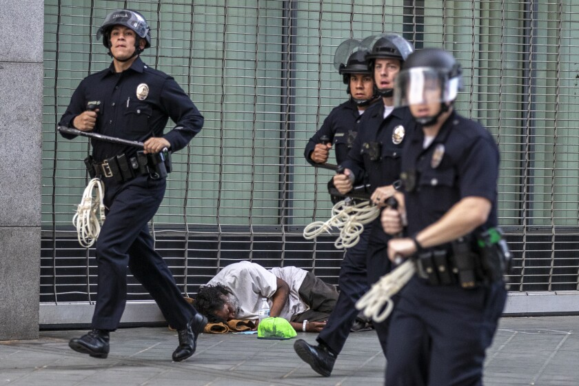 Los Angeles police officers carrying batons and zip ties rush along a sidewalk past a sleeping homeless man.