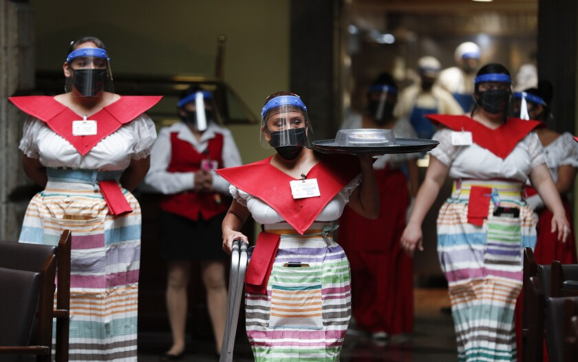 """A waitress at Mexico City's iconic """"Sanborns of the Azulejos"""" restaurant, wearing a mask and face shield to curb the spread of the new coronavirus, brings order for a patron in Mexico City, Wednesday, July 1, 2020. (AP Photo/Eduardo Verdugo)"""