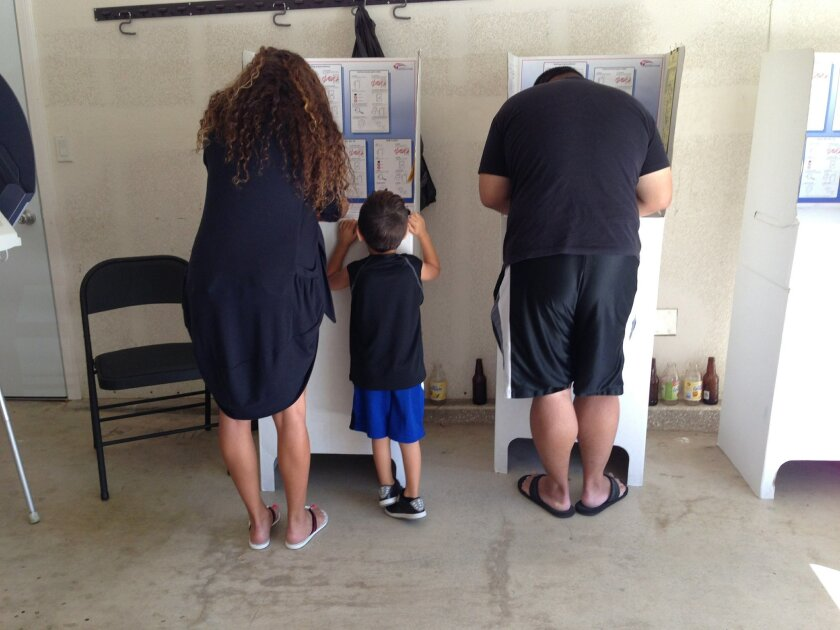 Gigi Modlin, left, with her son, Hayden Modlin looking, on, and Michael Roberts, right, vote in Mira Mesa Tuesday morning.