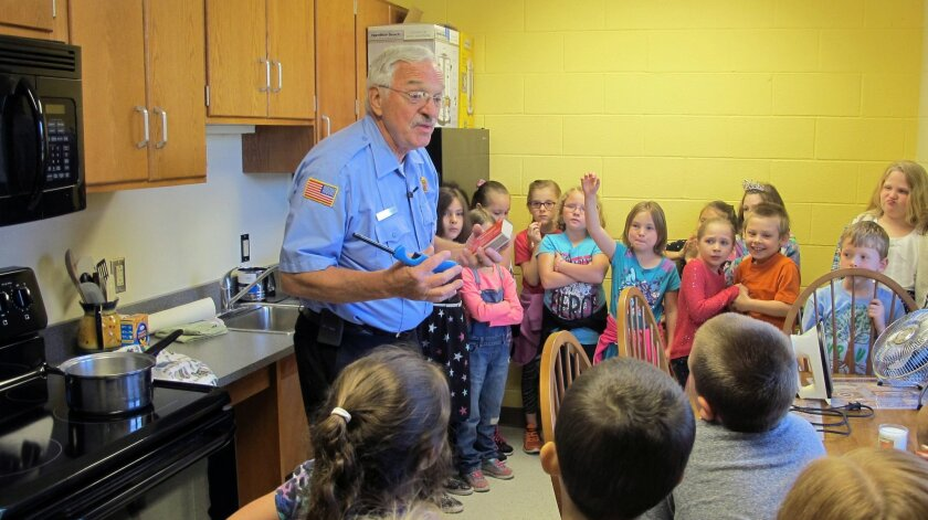 In this May 20, 2016 photo, Dewittville Volunteer Fire Department Chief Burl Swanson tells second-graders about kitchen fire hazards during a field trip to Chautauqua Children's Safety Education Village in Ashville, N.Y. The not-for-profit is one of dozens of safety villages in the United States an