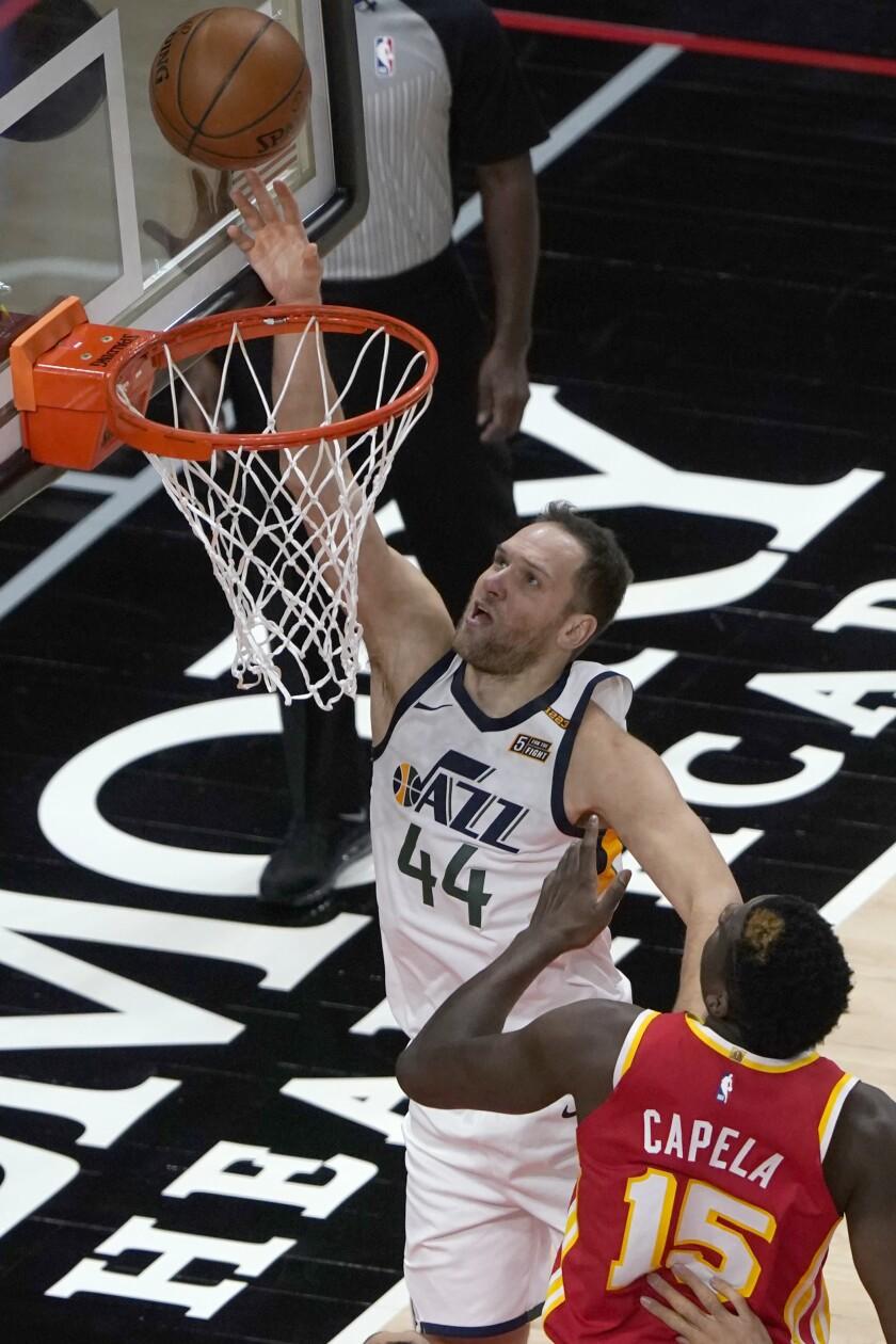 Utah Jazz forward Bojan Bogdanovic (44) goes up for a basket as Atlanta Hawks center Clint Capela (15) defends in the first half of an NBA basketball game Thursday, Feb. 4, 2021, in Atlanta. (AP Photo/John Bazemore)