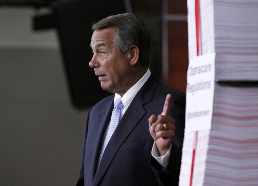 House Speaker John A. Boehner (R-Ohio) gestures toward a stack of paper representing the 20,000 pages of Affordable Health Care Act regulations during a news conference on Capitol Hill in Washington in May. Delays in issuing some of those rules led the Treasury Department to announce Tuesday that it was postponing enforcement of the law's requirement that employers provide insurance to their full-time workers.