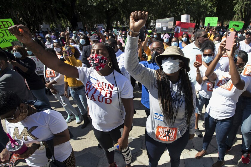 People hold a rally Friday in Brunswick, Ga., to protest the shooting of Ahmaud Arbery, a black man killed by a white father and son.