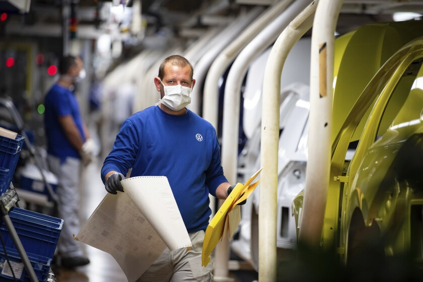 An employee walks past vehicles in production with a face mask in the VW plant in Wolfsburg, Germany, Monday, April 27, 2020. Volkswagen is gradually launch the production at important plants after the corona lockdown. (Swen Pfoertner/dpa via AP)