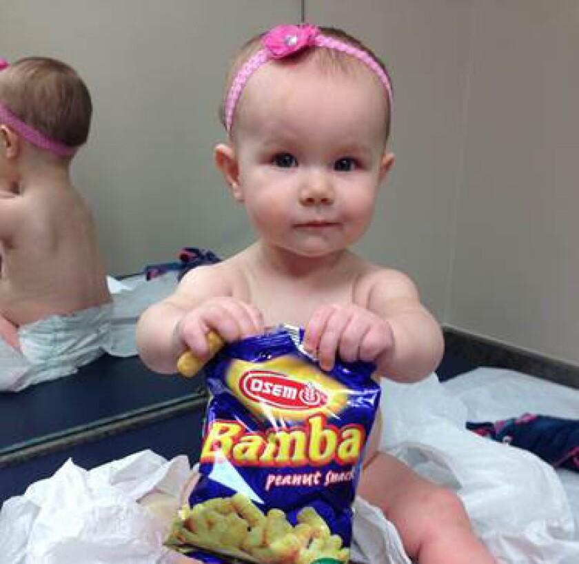 Una niña agarra una bolsa de la marca Bamba, una producto que contiene cacahuate y maíz inflado, y que se según un estudio podría haber ayudado a que los niños de Israel sufran menos casos de alergias a los cacahuates.