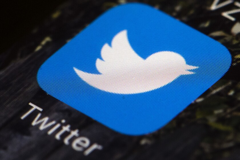 An illuminated smartphone screen shows a closeup of the Twitter app icon.