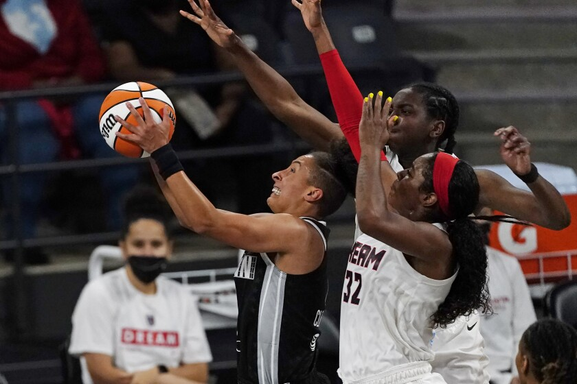 Minnesota Lynx' Layshia Clarendon is defended by Atlanta Dream center/forward Elizabeth Williams (1) and Atlanta Dream forward Cheyenne Parker (32) as she drives to the basket during the first half of their WNBA basketball game Wednesday, June 23, 2021, in College Park, Ga. (AP Photo/John Bazemore)