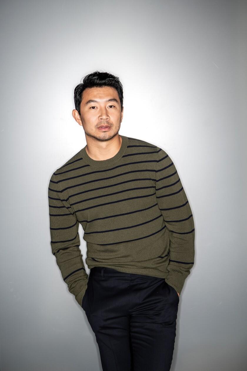 Portrait of actor Simu Liu in a green and black striped sweater