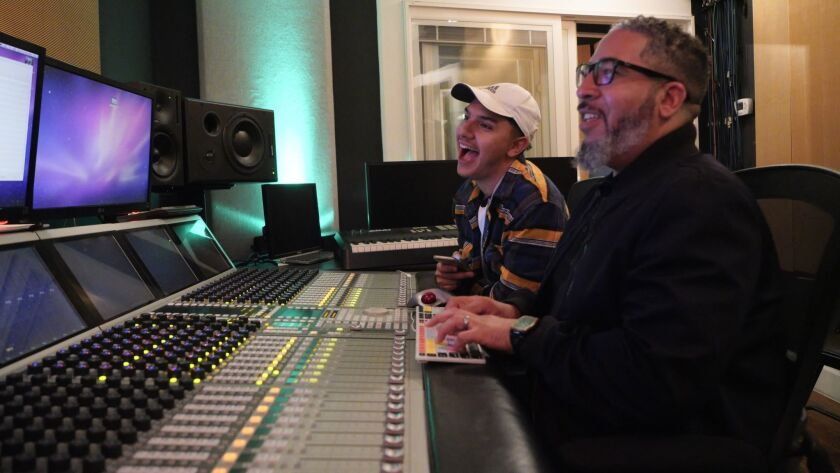 David Higarada while editing the music for his rap song enjoy a laugh with Joseph Mac, Director of P