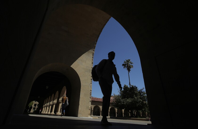 FILE - In this April 9, 2019, file photo, pedestrians walk on the campus at Stanford University in Stanford, Calif. The Education Department released a report Tuesday, Oct. 20, 2020, amid its effort to enforce a 1986 law requiring U.S. universities to disclose gifts and contracts from foreign sources. The department's findings are primarily based on investigations it has opened at 12 schools, including Harvard, Yale, Stanford and Georgetown universities. (AP Photo/Jeff Chiu, File)