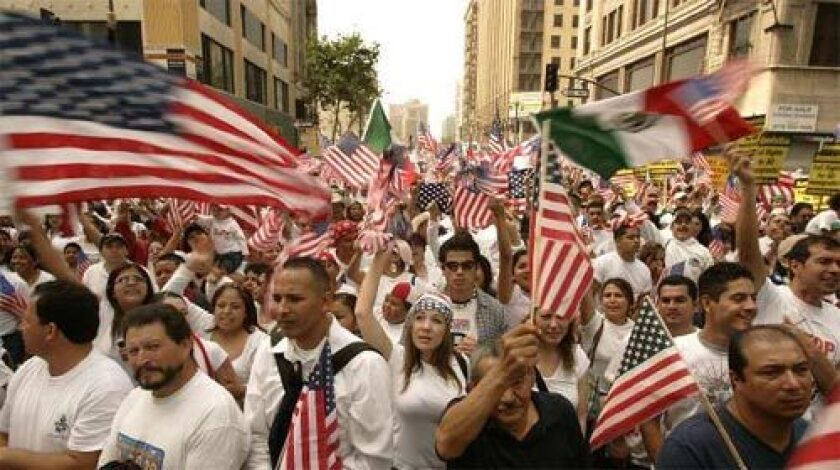RAISING THEIR BANNERS: Immigrants and supporters gather at Olympic Boulevard and Broadway in one of two Los Angeles marches that attracted hundreds of thousands of demonstrators.
