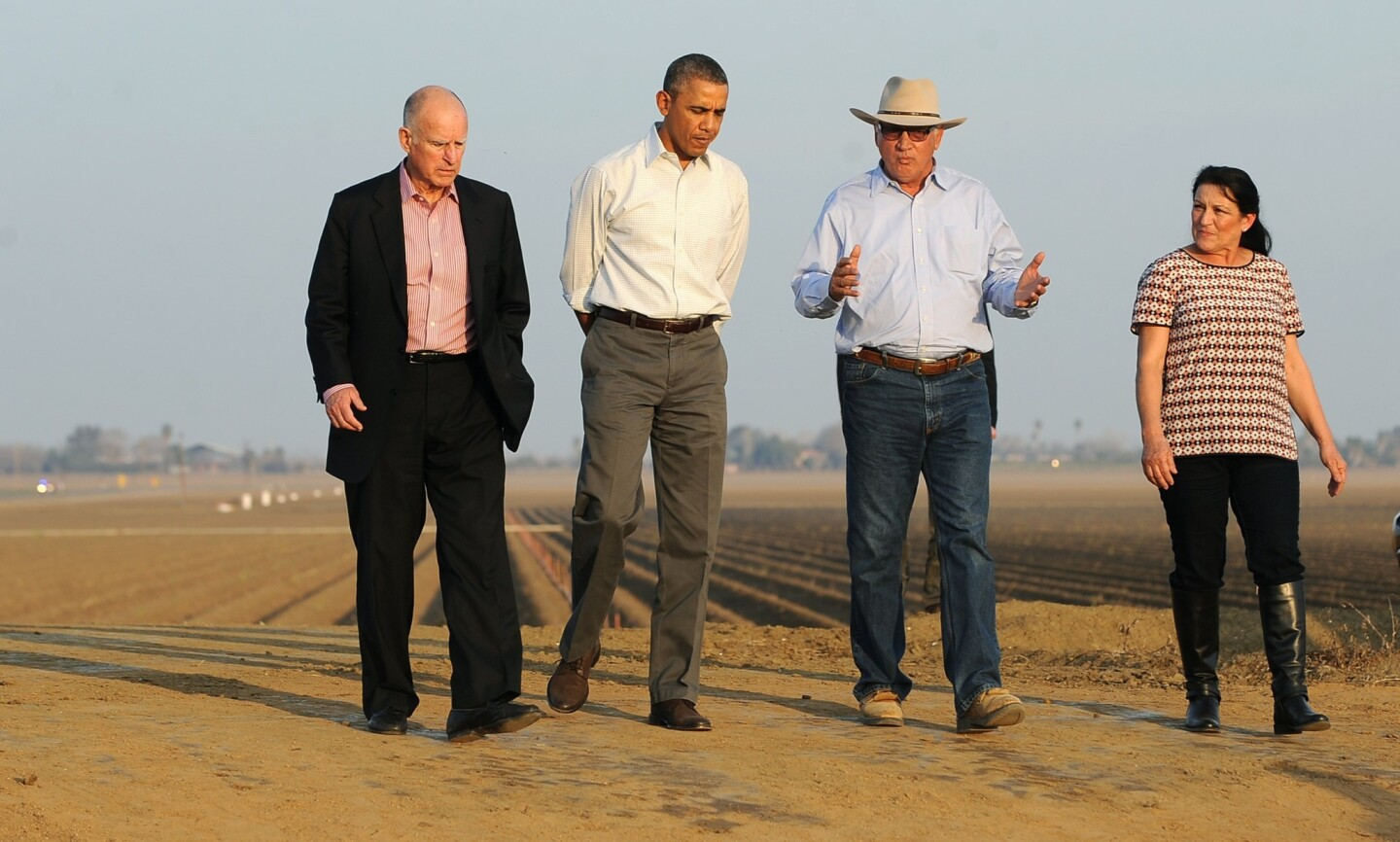 President Obama walks with Gov. Jerry Brown, left, and Joe and Maria Del Bosque on the Del Bosques' farm in Los Banos, Calif.